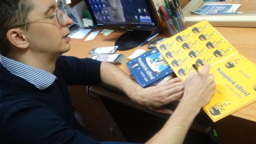 Jakub Skworz podpisuje składa autograf w książce