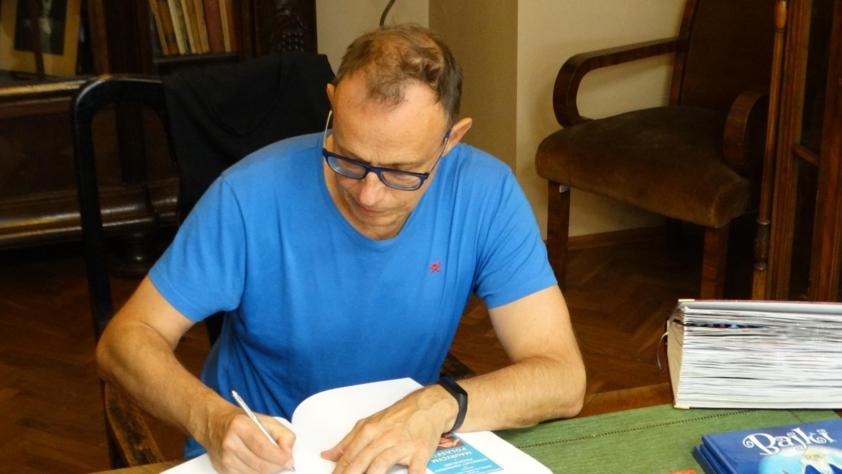 Maurycy Polaski wpisuje dedykacje do kroniki bocheńskiej biblioteki